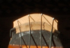 This image taken at a very low angle down the fingerboard shows the close relationship which should exist between the profiles of the bridge and fingerboard.